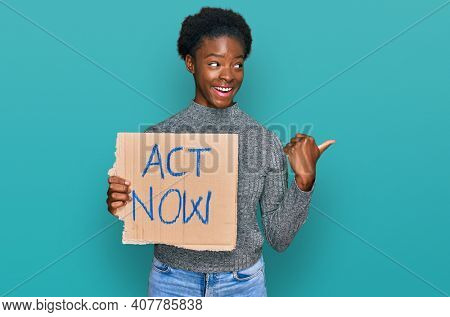 Young african american girl holding act now banner pointing thumb up to the side smiling happy with open mouth