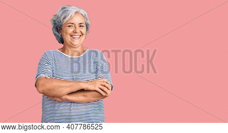 Senior woman with gray hair wearing casual striped clothes happy face smiling with crossed arms looking at the camera. positive person.