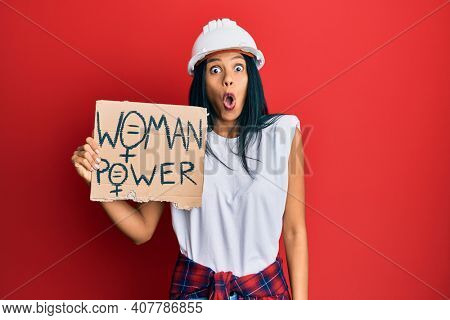 Young african american woman wearing architect hardhat holding woman power banner scared and amazed with open mouth for surprise, disbelief face
