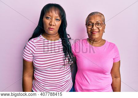 Hispanic family of mother and daughter hugging together with love thinking attitude and sober expression looking self confident