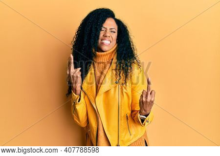 Middle age african american woman wearing wool winter sweater and leather jacket showing middle finger doing fuck you bad expression, provocation and rude attitude. screaming excited