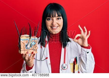 Young hispanic doctor woman holding model of human anatomical skin and hair doing ok sign with fingers, smiling friendly gesturing excellent symbol
