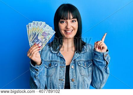 Young hispanic woman holding 100 romanian leu banknotes smiling happy pointing with hand and finger to the side