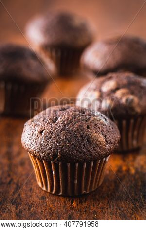 Chocolate muffins. Sweet dark cupcakes on wooden table.