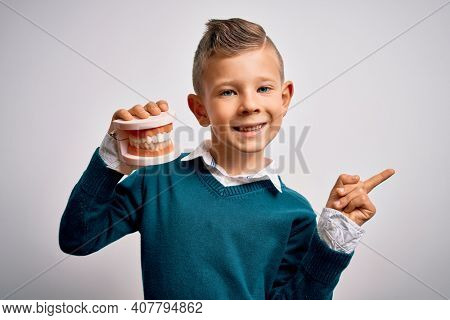 Young little caucasian kid holding dental prosthesis teeth denture over isolated background very happy pointing with hand and finger to the side