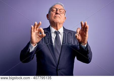 Grey haired senior business man wearing glasses and elegant suit and tie over purple background relaxed and smiling with eyes closed doing meditation gesture with fingers. Yoga concept.