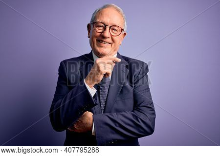 Grey haired senior business man wearing glasses and elegant suit and tie over purple background looking confident at the camera smiling with crossed arms and hand raised on chin. Thinking positive.