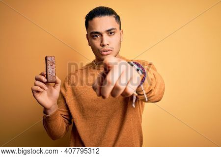 Young brazilian man eating healthy energy bar with protein over isolated yellow background pointing with finger to the camera and to you, hand sign, positive and confident gesture from the front