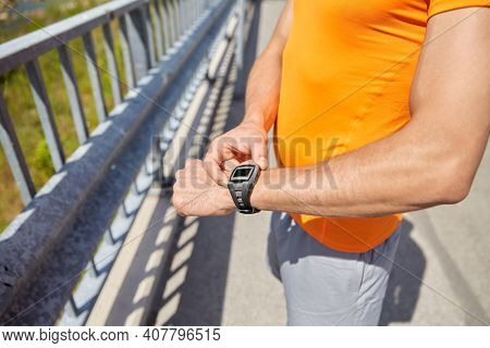 fitness, sport and healthy lifestyle concept - close up of young man with fitness tracker at seaside