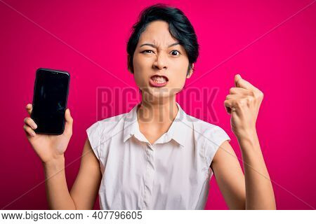 Young beautiful asian girl holding smartphone showing screen over isolated pink background annoyed and frustrated shouting with anger, crazy and yelling with raised hand, anger concept
