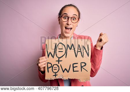 Young beautiful activist woman asking for women rights holding banner with power message screaming proud and celebrating victory and success very excited, cheering emotion