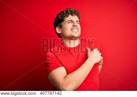 Young blond handsome man with curly hair wearing casual t-shirt over red background Suffering of neck ache injury, touching neck with hand, muscular pain
