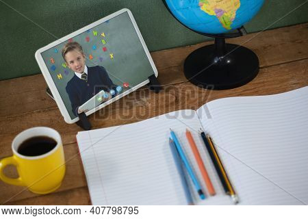 Caucasian schoolboy learning on tablet screen on desk during video call. Online education staying at home in self isolation during quarantine lockdown.
