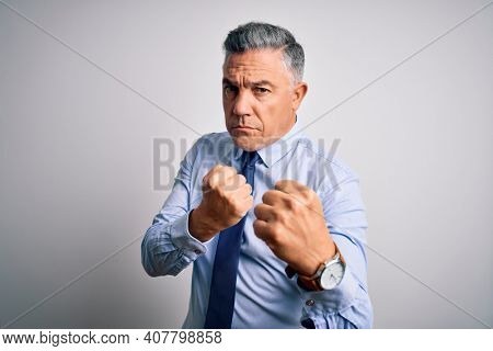 Middle age handsome grey-haired business man wearing elegant shirt and tie Ready to fight with fist defense gesture, angry and upset face, afraid of problem