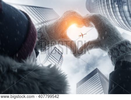 Woman making heart symbol with hands wearing gloves and airplane