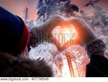 Woman making heart symbol with hands wearing gloves, sunny winter evening