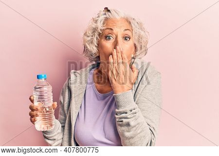 Senior grey-haired woman wearing sportswear drinking bottle of water covering mouth with hand, shocked and afraid for mistake. surprised expression