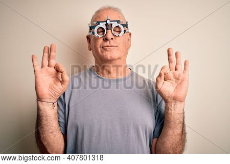 Middle age hoary man controlling vision wearing optometry glasses over white background relax and smiling with eyes closed doing meditation gesture with fingers. Yoga concept.