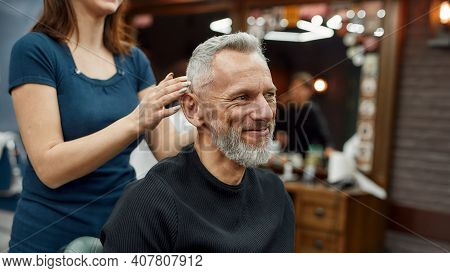 Happy Mature Bearded Man Looking In The Mirror And Smiling While Female Barber Showing The Result Of