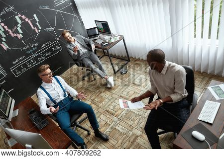 High-angle View Of Three Traders Sitting By Desks In Front Of Computer Monitors While Working In The