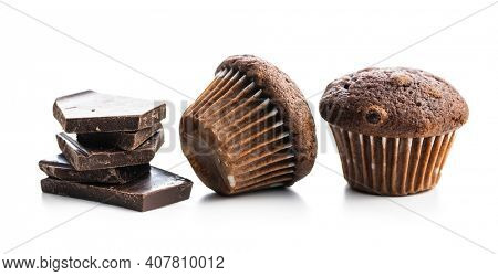 Chocolate muffins and chocolate bars. Sweet dark cupcakes isolated on white background.