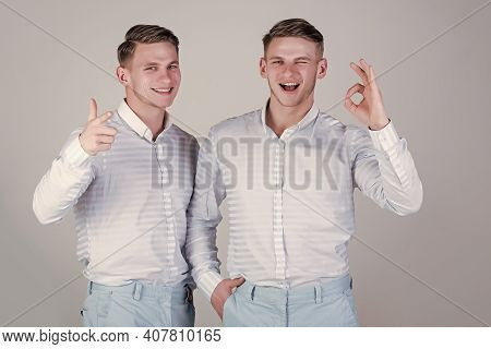 Happy Men Together. Two Brothers Showing Thumbs Up And Ok Gestures. Models Winking And Smiling On Gr