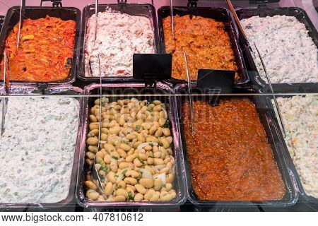 Variety Of Fresh Salads On A Showcase In Supermarket. Take-out Food In Showcase Window. Food For Hom