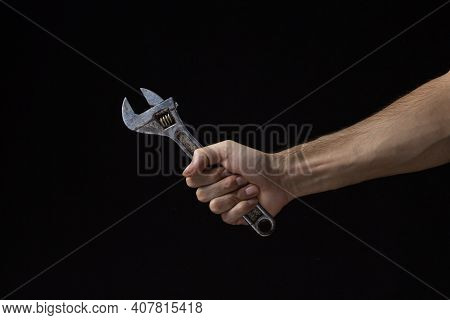 Adjustable Wrench On A Black Background. Old Work Tool. A Man\'s Hand Holds An Adjustable Wrench.