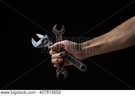 Wrench And Adjustable Wrench On A Black Background. Old Work Tool. A Male Hand Holds A Spanner And A