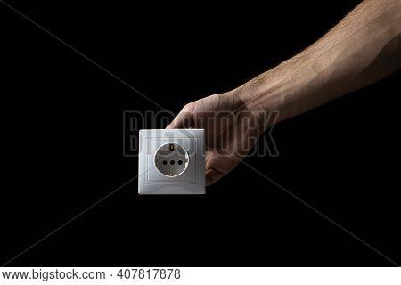 White Socket On A Black Background. Flush-mounted White Socket. Male Hand Holds White Socket