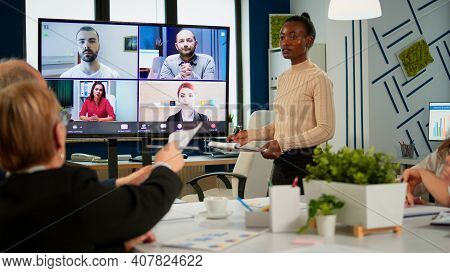 African Woman Discussing With Remote Managers On Video Call Presenting New Partners On Webcam. Confi