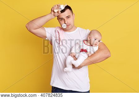 Young Caucasian Father Feeding Newborn Baby From Bottle Milk. Man Parent Holding Rocking Daughter. L