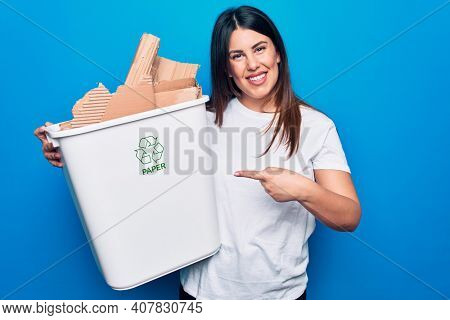 Young beautiful woman recycling cardboard on wastebasket to care environment smiling happy pointing with hand and finger