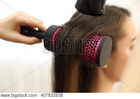 Stylist Drying Client's Hair In Beauty Salon, Closeup
