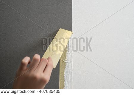 Hand Taking Off Masking Tape From The Wall After Painting