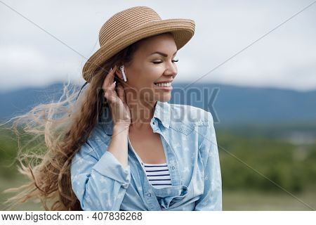 A Beautiful Romantic Girl In A Big Straw Hat And With White Headphones In Her Ears, Enjoys The Music