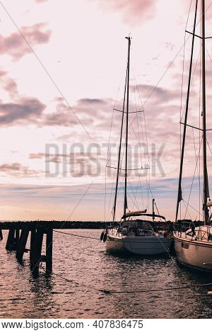 Sunset Or Sunrise At The Pier. A Pier With Boats In The Rays Of The Rising Sun. Fishing Boats At Sea