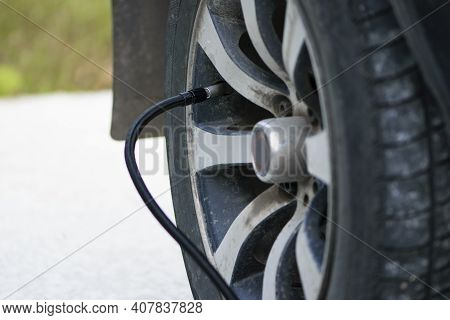 Inflating Car Wheels With A Compressor. Rubber Hose From The Pump, Filling The Tire, Filling The Car