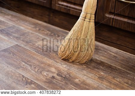 Cleanliness And Order At Home, A Broom Of Sorghum For Sweeping Is On The Floor Against The Wall In T