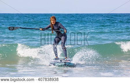 Young Woman With Wetsuit Swimming On Stand Up Paddle Board. Water Sports , Active Lifestyle. Sup Sur