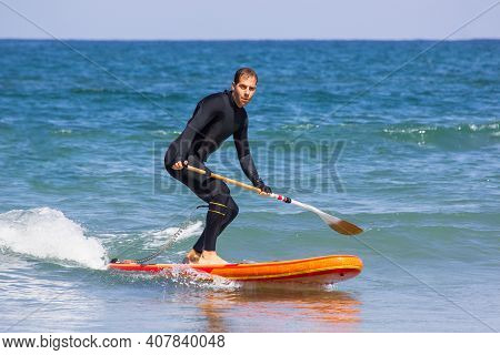 Sup Stand Up Surf Man With Wetsuit With Paddle In The Sea. Surfer On Stand Up Paddle Board On Wave.