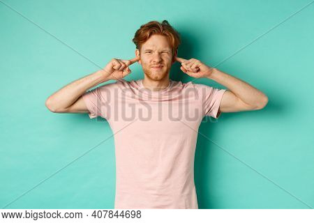 Annoyed Young Man With Red Hair And Beard Shut His Ears And Grimacing, Disturbed By Loud Bothering S