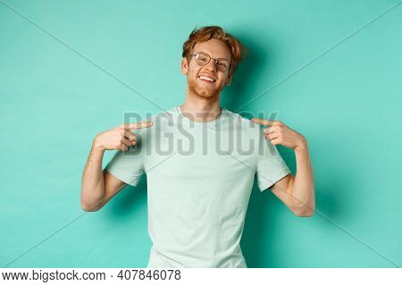 Confident Redhead Man In Glasses And T-shirt, Smiling With Smug Face And Pointing At Himself, Braggi