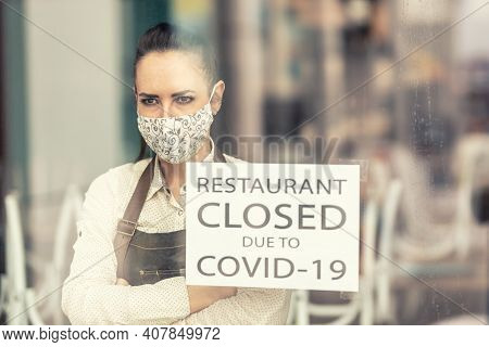 Upset Restaurant Owner Stands With Arms Crossed On Her Chest Next To A Sign Saying Restaurant Closed
