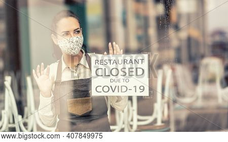 Waitress In A Closed Restaurant Due To Covid-19 Wears Face Mask Looking Out Of The Window.