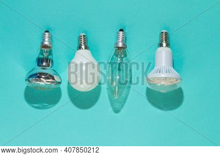 Different Types Of Light Bulbs On A Blue Background. Halogen, Led, Incandescent Lamp Lies On The Sur