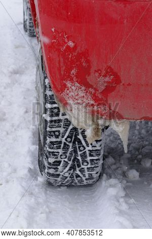 Icicles On Rear Fender Red Car In Winter. Spiked Tire For Snow Riding. Cold And Bad Weather Driving
