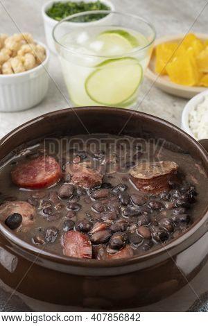 Traditional Brazilian Feijoada With Rice, Kale, Orange, Cracklings And Caipirinha.