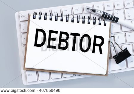 Debtor. Text On White Paper On White Keyboard