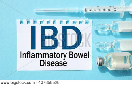 Ibd - Inflammatory Bowel Disease. Text On White Paper On A Blue Background. Ampoules, Syringe